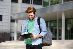 Exterior derecho del estudiante universitario de sexo masculino con la libreta y el bolso Fotos de archivo libres de regalías