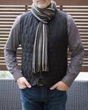 Exterior derecho del hombre maduro con un chaleco y una bufanda de las lanas en invierno Foto de archivo libre de regalías