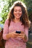 Exterior derecho sonriente de la muchacha adolescente con el móvil y los auriculares Foto de archivo