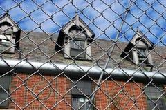 Exterior do embarcado acima e construção abandonada do hospital do asilo do tijolo com as janelas quebradas cercadas pela cerca d Imagem de Stock Royalty Free