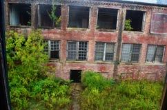 Exterior do embarcado acima e construção abandonada do hospital do asilo do tijolo com janelas quebradas fotos de stock royalty free