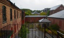 Exterior do embarcado acima e construção abandonada do hospital do asilo do tijolo com janelas quebradas foto de stock