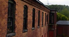 Exterior do embarcado acima e construção abandonada do hospital do asilo do tijolo com janelas quebradas fotografia de stock