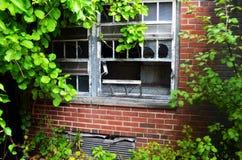Exterior do embarcado acima e construção abandonada do hospital do asilo do tijolo com janelas quebradas imagem de stock