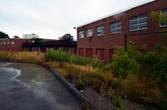 Exterior do embarcado acima e construção abandonada do hospital do asilo do tijolo com janelas quebradas imagens de stock