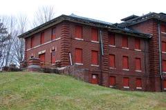 Exterior do embarcado acima e construção abandonada do hospital do asilo do tijolo com janelas quebradas imagem de stock royalty free