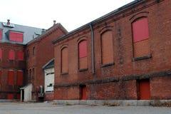 Exterior do embarcado acima e construção abandonada do hospital do asilo do tijolo com janelas quebradas imagens de stock royalty free