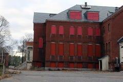 Exterior do embarcado acima e construção abandonada do hospital do asilo do tijolo com janelas quebradas foto de stock royalty free