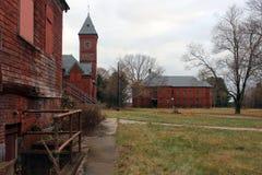 Exterior do embarcado acima e construção abandonada do hospital do asilo do tijolo com janelas quebradas fotografia de stock royalty free
