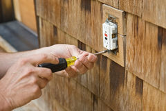 Exterior Electrical Outlet. Man using screwdriver to remove electrical outlet stock image