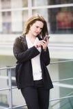 Exterior ereto da jovem mulher e texting no telefone imagem de stock
