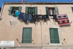 Exterior of the facade of a residential building with washed clothes hanging outside in Murano, Italy. Royalty Free Stock Photos