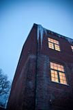 Exterior of factory in Winter. Low angle view of lit factory in Winter with icicles hanging from roof stock photos
