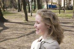 Exterior feliz sonriente de la mujer bastante rubia de los jóvenes en cierre del parque de la primavera para arriba, concepto de  Foto de archivo