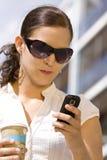 Exterior femenino del asunto joven con el teléfono móvil Foto de archivo libre de regalías