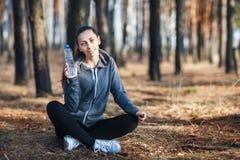 Exterior femenino sonriente feliz joven de la aptitud del deporte en parque Mujer que sostiene una botella de agua fría en su man foto de archivo