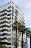 Exterior front view, Hollywood Versailles Tower, California. Exterior full front view of Hollywood Versailles Tower with palm tree leaf hanging on the street of stock photos