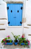 Exterior of Greek house. With white walls, blue shuttered windows and plants Royalty Free Stock Images