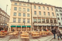 Exterior of historical Bavarian restaurant, wooden outdoor furniture and walking people Royalty Free Stock Photography