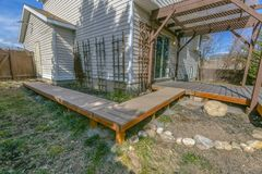 Exterior of a home with a wooden walkway and deck on the yard. A pergola is constructed over the deck with a reflective glass door that leads inside the home royalty free stock photography