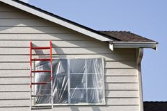 Exterior House Painting. Section of a residential house / home with windows covered in painter's plastic, ladder in front of window, preparation for exterior Royalty Free Stock Photo
