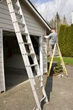 Exterior House Painting. Professional house painter standing on a ladder masking off residential exterior home / house fixtures in preparation for a fresh coat Stock Image