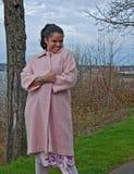 Exterior juguetón de la mujer de Multi_Ethnic con la capa rosada Fotografía de archivo