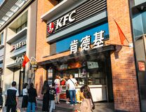 Exterior of KFC restaurant with people in China and flag royalty free stock photography