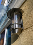 Exterior Light. A modern elecrical light fitting mounted on a textured wall stock images