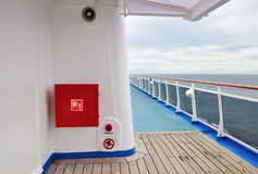 Exterior of luxury cruise ship with fire hose reel. White painted wall of a luxury cruise ship exterior image, with fire hose reel on a wall. Rails and view of Stock Photos