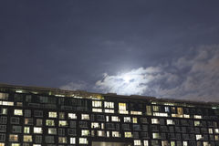The exterior of a modern apartment block at night. With the moon rising overhead Royalty Free Stock Photography