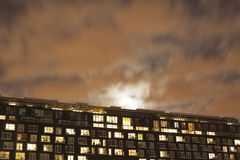 The exterior of a modern apartment block at night. With the moon rising overhead Stock Image