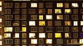 The exterior of a modern apartment block at night. Time-lapse of the exterior of a modern apartment block at night stock footage