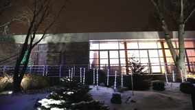Exterior of modern house or restaurant, the Christmas lights are lit on the trees, in the night sky, camera movement. Tree decorated with Christmas lights stock video