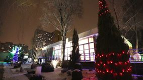 Exterior of modern house or restaurant, the Christmas lights are lit on the trees, in the night sky, camera movement. Tree decorated with Christmas lights stock video footage