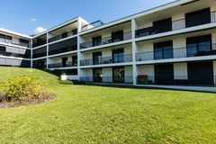 Exterior modern white condominium building with lots of lawn,. Nobody inside stock photography