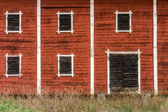 Exterior of old abandoned decayed red barn with closed wooden window shutters. Stock Image