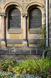 Exterior of old church. Exterior of old stone church with stained glass windows, flowers in foreground royalty free stock photos