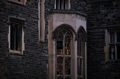 Exterior of an old gothic building with stone walls and bay window in the evening dusk.  stock image