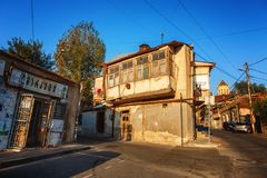 Exterior of an old house with wood balcony in the old town of Tbilisi, Georgia. Tbilisi, Georgia - 8 October 2016: Exterior of an old house with wood balcony in Stock Photo