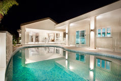 Exterior patio and swimming pool. Illuminated undercover exterior patio and crystal clear refreshing swimming pool at an upmarket residence Royalty Free Stock Photo