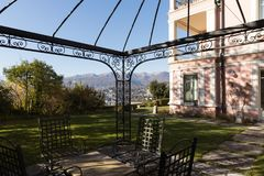 Exterior of ancient villa. Nobody inside. Exterior of a pink vintage villa. Autumn garden with wrought iron chairs and tables Stock Image