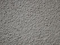 Exterior plaster wall surface. Detail of grey bumpy plaster surface of exterior wall in sunny day, close-up royalty free stock photography