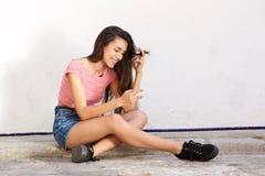 Exterior que se sienta adolescente sonriente que mira el teléfono móvil Imagen de archivo libre de regalías