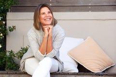 Exterior que se sienta de la mujer feliz que mira lejos fotos de archivo libres de regalías