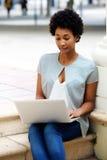 Exterior que se sienta de la mujer joven que trabaja en el ordenador portátil Imágenes de archivo libres de regalías