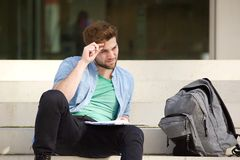 Exterior que se sienta del estudiante universitario de sexo masculino que piensa con la libreta Fotos de archivo libres de regalías