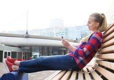 Exterior que se sienta sonriente de la mujer del viaje que mira el teléfono móvil Imágenes de archivo libres de regalías