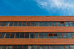Exterior of red brick building. Exterior architecture of red brick building under blue sky Royalty Free Stock Images