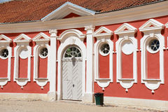 Exterior of the red painted stables building windows next to Rundale palace in Pilsrundale, Latvia. PILSRUNDALE, LATVIA - JULY 27, 2015: Exterior of the red Stock Images